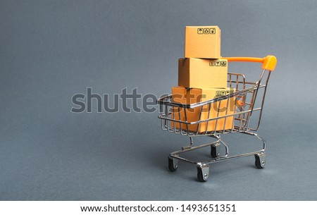 A pile of cardboard boxes in a supermarket trolley. concept of shopping in the online store . E-commerce, sales and sale of goods through online trading platforms. Consumer society. Purchasing power Royalty-Free Stock Photo #1493651351