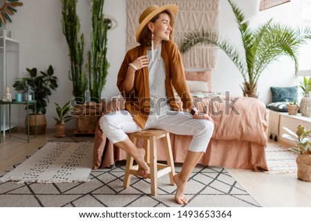 Fashionable image of happy woman in straw hat posing over bohemian interior background. Straw hat , linen  closes. Natural make up. Full lengt. #1493653364