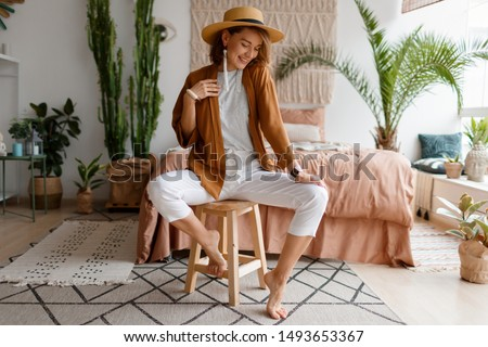 Cozy home atmosphere. Stylish woman in linen clothes sitting on chair over bed and home plants. Soft colors. #1493653367