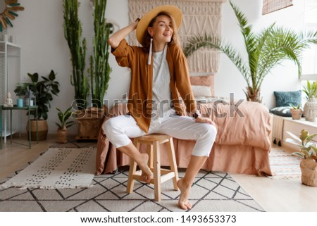 Cozy home atmosphere. Stylish woman in linen clothes sitting on chair over bed and home plants. Soft colors. #1493653373