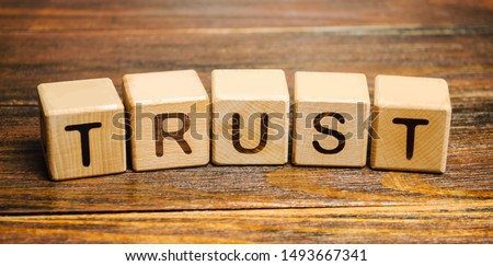 Wooden blocks with the word Trust. Trust relationships between business partners, friends, relatives. Respect and authority. Confidence in a person. Reliable partner #1493667341