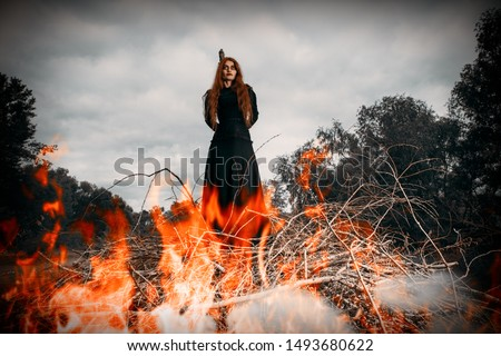 A portrait of an angry witch tied for incineration. Magic, dark force, spell.  Royalty-Free Stock Photo #1493680622