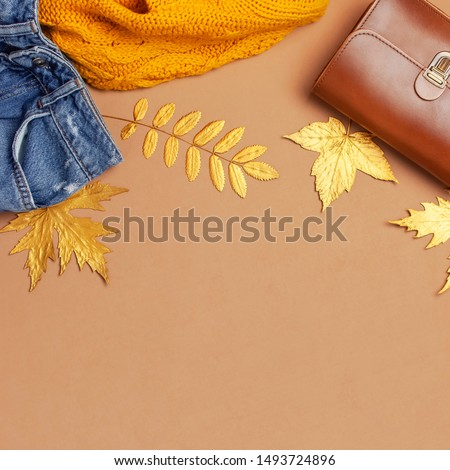 Autumn Fashion Concept. Brown leather women bag, orange knitted sweater, blue jeans, golden autumn leaf on brown background top view flat lay copy space. Fashionable women's accessories Female Clothes #1493724896