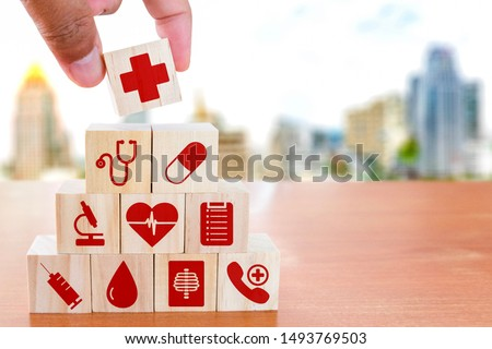 Hand arranging wood block stacking with icon healthcare medical on wooden table against blurred building background , Medical health-care and Insurance for your health concept. #1493769503
