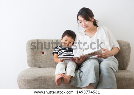 Pregnant woman reading a picture book for a boy