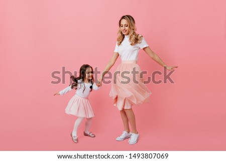 Positive blonde mom and dark-haired daughter in lush romantic skirts are dancing boogie woogie on pink background #1493807069
