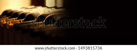 Bottles of red wine on a wooden shelf, panoramic banner with black background Royalty-Free Stock Photo #1493815736