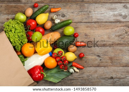 Flat lay composition with overturned paper bag and groceries on wooden table. Space for text #1493858570