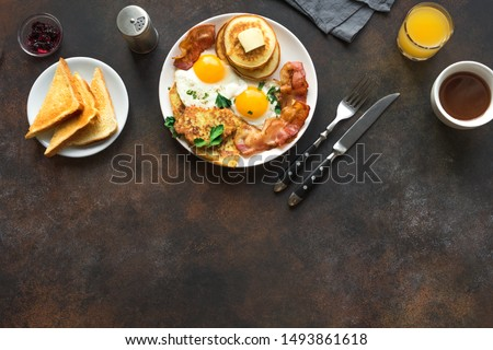 Full American Breakfast on white, top view, copy space. Sunny side fried eggs, roasted bacon, hash brown, pancakes, orange juice and coffee for breakfast. #1493861618