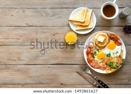 Full American Breakfast on wooden, top view, copy space. Sunny side fried eggs, roasted bacon, hash brown, pancakes, orange juice and coffee for breakfast. #1493861627