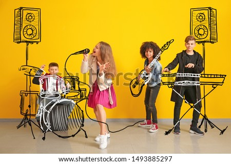 Teenage musicians with drawing instruments playing against color wall #1493885297