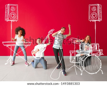 Teenage musicians with drawing instruments playing against color wall