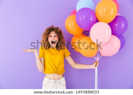 Image closeup of attractive delighted woman rejoicing while posing in multicolored air balloons isolated over violet background #1493888033