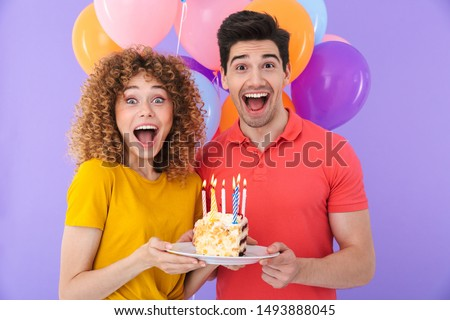 Image of excited couple man and woman celebrating birthday with multicolored air balloons and piece of cake isolated over violet background