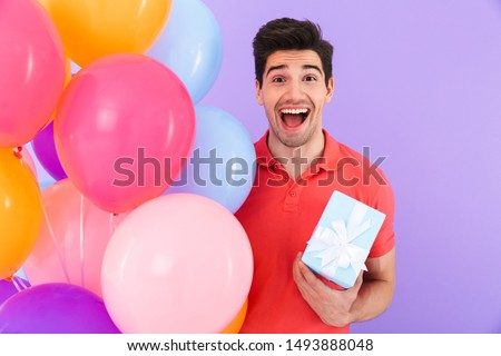 Image of happy joyful man celebrating birthday with multicolored air balloons and gift box isolated over violet background