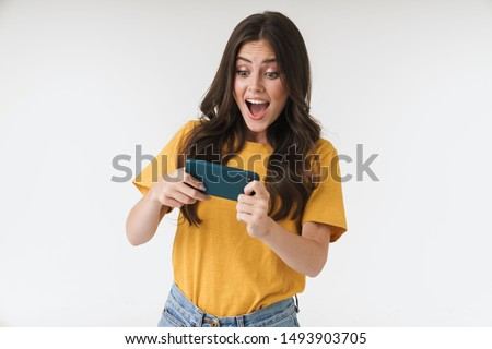 Photo of emotional positive young woman posing isolated over white wall background play games by mobile phone.