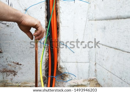 The electrician conducts electrical work on the current grounding of the current drain. #1493946203