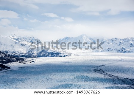 Eagle Peak, Alaska - April 10, 2017: An extreme wide aerial view of Eagle Peak mountains in Alaska with cloudy shades crossing the frozen lake #1493967626