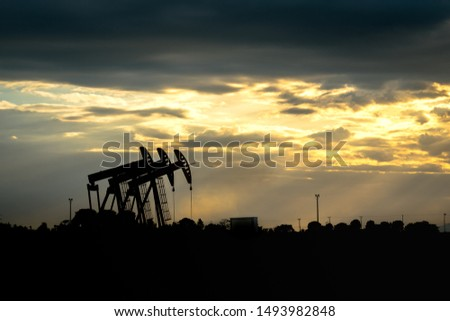 Silhouette or shadow shape of Crude oil pump or Beam pump which is using for enhance crude oil production from the well, photo taken during the beautiful orange sunset with cloudy sky background.