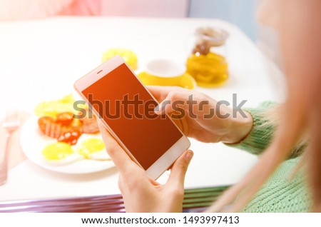 Female taking pictures with cell phone camera. Fried eggs with bacon and vegetables
