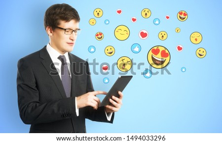 Portrait of handsome young businessman using tablet with emotive on subtle background. Communication and emotion concept #1494033296