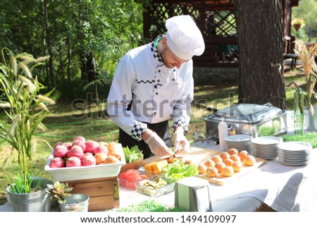 Chef man preparing snacks for the holiday. The concept of servicing holidays and corporate parties. Field service. #1494109097