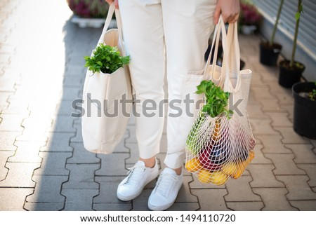 Girl is holding mesh shopping bag and cotton shopper with vegetables without plastic bags at farmers market. Zero waste, plastic free concept. Sustainable lifestyle. Banner #1494110720