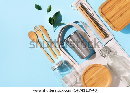 Cotton bags, glass jar, bottle, metal cup, straws for drinking, bamboo cutlery and boxes on blue background. Sustainable lifestyle. Zero waste, plastic free shopping concept. #1494113948
