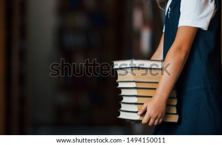 Particle view of little girl holds many books in hands in the library.