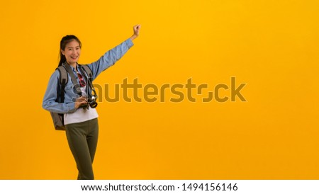 Summer travel, journey, vacation concept : Portrait photo of young attractive Asian tourist woman in summer casual clothes preparing for travel. studio shot on yellow background. #1494156146