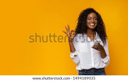 Definitely like it. Cute afro girl showing okay gesture, holding smartphone and gesturing OK, free space