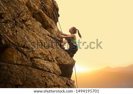 Beautiful Woman Climbing on the High Rock at Foggy Sunset in the Mountains. Adventure and Extreme Sport Concept #1494195701