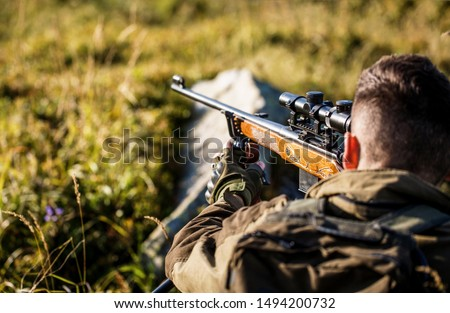 Hunting period. Male with a gun. Close up. Hunter with hunting gun and hunting form to hunt. Hunter is aiming. Shooter sighting in the target. The man is on the hunt. Hunt hunting rifle. Hunter man. #1494200732