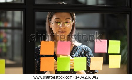 Serious focused young female coach teacher student asian business woman working on project strategy plan writing target tasks creative ideas on sticky post it notes on glass scrum board office wall #1494206042