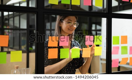 Young smiling asian business woman mentor leader write tasks creative ideas on sticky post it notes on glass wall, vietnamese female coach planning project corporate management on sticker scrum board #1494206045