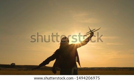 Happy girl runs with a toy airplane on a field in the sunset light. children play toy airplane. teenager dreams of flying and becoming a pilot. girl wants to become a pilot and astronaut. Slow motion #1494206975