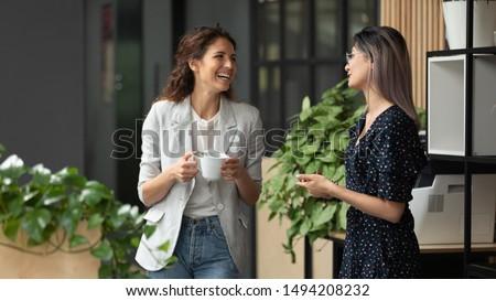 Happy positive female colleagues joking laughing during coffee break in work space, smiling diverse women business team talking having fun enjoy conversation good friendly relations walking in office #1494208232
