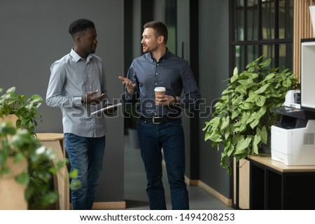 Diverse friendly male partners colleagues talking walking in modern office hallway, young african american and caucasian business men discussing common project work meeting in company work space Royalty-Free Stock Photo #1494208253