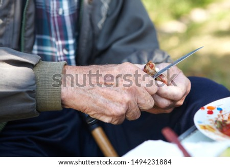 Poverty and bread. Elderly poor man eating bread #1494231884