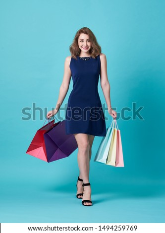 Happy beautiful young woman in blue dress and hand holding shopping bag isolated over blue background. #1494259769