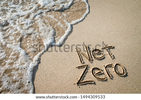 Net Zero message for energy consumption handwritten on smooth sand beach with oncoming wave  Royalty-Free Stock Photo #1494309533