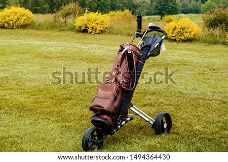 Leather stylish brown bag with golf clubs on a special cart on the golf course.