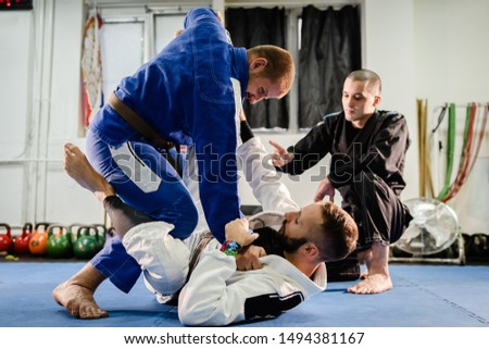 Brazilian JIu Jitsu BJJ private class professor of the martial arts academy working on the technique details with his students black and brown belts training open guard in kimono gi Royalty-Free Stock Photo #1494381167