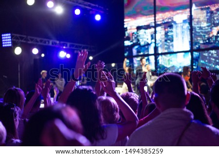 Rear view of crowd with arms outstretched at concert. cheering crowd at rock concert. silhouettes of concert crowd in front of bright stage lights. Crowd at music concert, audience raising hands up #1494385259