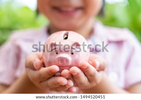 hands of Asian children holding the pink color of a piggy bank and saving money for future education ideas.Cute Little boy Having Fun with  Piggy Bank outdoor nature background.selective focus