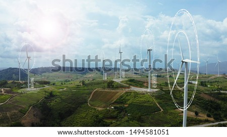 Aerial view of windmills with digitally generated holographic display tech data visualization. Wind power turbines generating clean renewable energy for sustainable development in a green ecologic way #1494581051