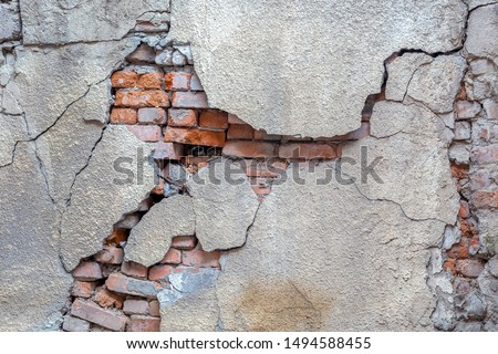 Large crack on the wall of an old brick house, crumbling plaster and broken, cracked bricks. Background image Royalty-Free Stock Photo #1494588455
