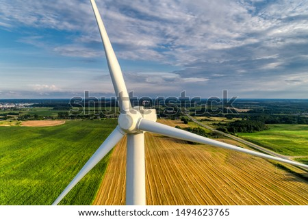 Wind power station. Wind generators stand in agricultural fields. Wonderful landscape shot from a great height. Modern green energy. Aerial view. #1494623765