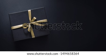 One gift wrapped in dark black paper with luxury bow on dark background. Horizontal with copy space. Banner #1494658364