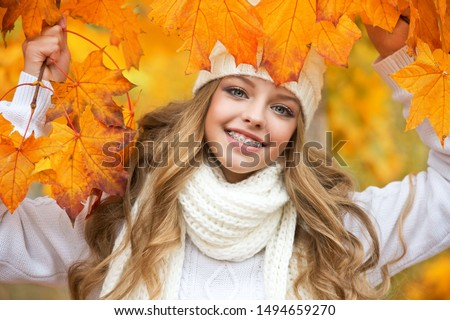 Portrait of beautiful young woman walking outdoors in autumn. Girl with autumn yellow leaf in knitted hat and sweater.  Portrait of a girl with orthodontic appliance. #1494659270